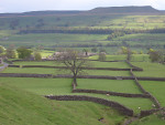A view looking down over Askrigg and across Wensleydale towards Addlebrough